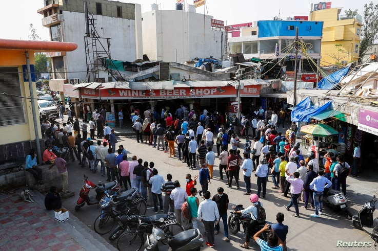 People queue outside a wine store to buy liquor after Delhi government ordered a six-day lockdown to limit the spread of the…