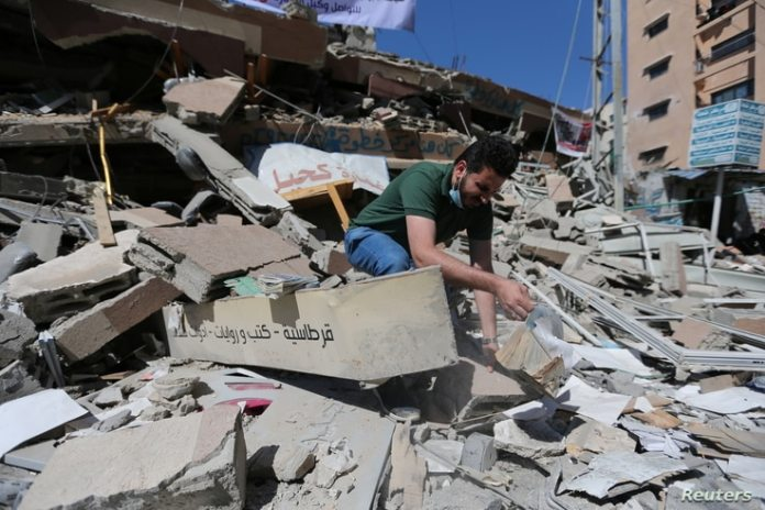 Palestinian Shaban Esleem inspects the rubble of his bookstore destroyed during Israeli airstrikes during the Israeli-Palestinian fighting, in the city of Gaza, May 24, 2021.