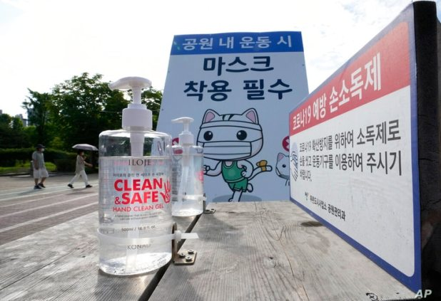 Bottles of hand sanitizer are displayed for use at a park in Goyang, South Korea, Tuesday, June 15, 2021. The banner reads …