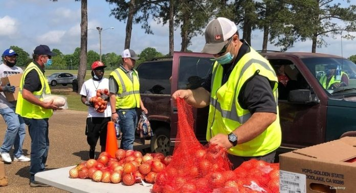 Volunteers from the Mississippi Food Network and Tyson Foods Company load vehicles with onions and other food in Forest, Mississippi.  Materials were distributed to more than 300 families.