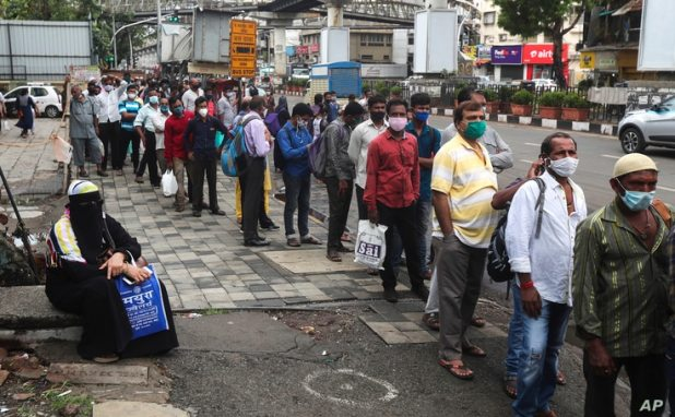 People wearing face masks as a precaution against the coronavirus wait at a bus stop in Mumbai, India, June 7, 2021.