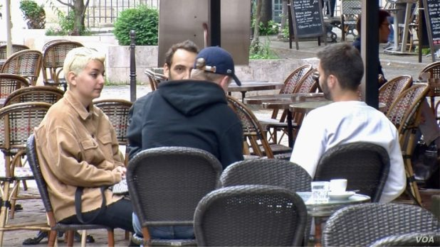 Young people having coffee in Paris. France reopened bars and restaurants mid-may as coronavirus cases dropped.