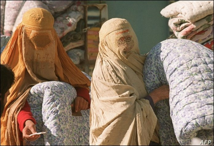 Afghan women, seen in this photo from November 19, 1996, in Kabul, wearing burqas fitted by the Taliban, wait during a winter respite...