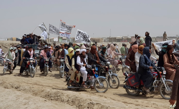 Supporters of the Taliban carry their signature white flags after the Taliban said they seized the Afghan border town of Spin Boldaka across from the town of Chaman, Pakistan, July 14, 2021.
