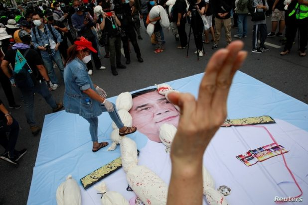 A protester places mock body bags representing COVID-19 victims on a picture of Thai Prime Minister Prayut Chan-O-Cha during an anti-government protest in Bangkok, Thailand, July 18, 2021.