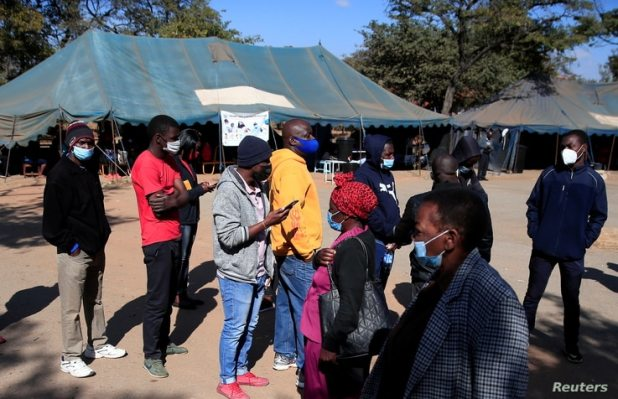 FILE - People queue to be vaccinated against COVID-19 at a clinic in Harare, Zimbabwe, July 8, 2021.