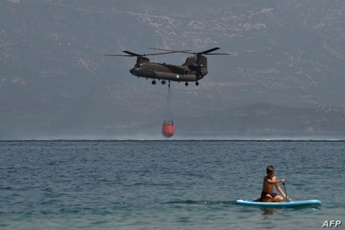 A Ch-47D Chinook helicopter is seen by a paddleboarder as it fills with water during a firefight near Lambiri Beach…
