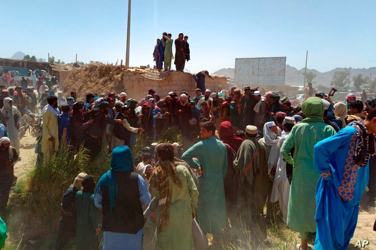 Taliban fighters and Afghans gather around the body of a member of the security forces who was killed, inside the city of Farah…