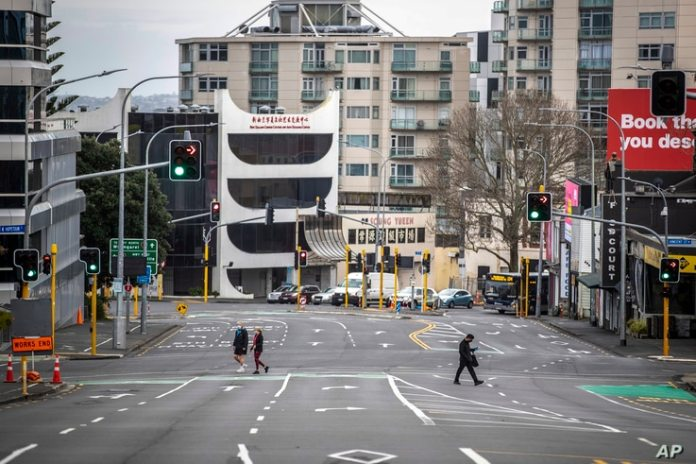On August 27, 2021, people pass through almost empty streets in the Auckland Central Business District, New Zealand.
