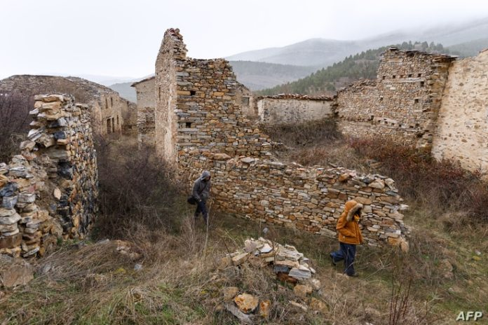 File - People walk in the uninhabited village of Elidialcardo, in the northern Spanish province of Soria, on February 2, 2011.