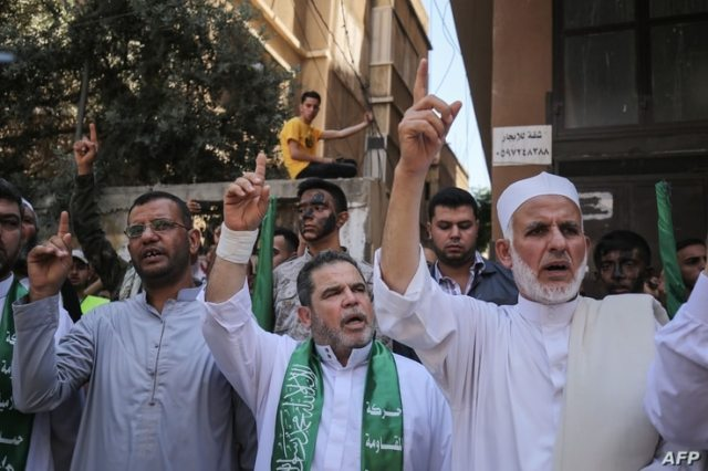 Palestinian Hamas supporters take part in a protest against Israel's plan to annex parts of the occupied West Bank, in Khan…