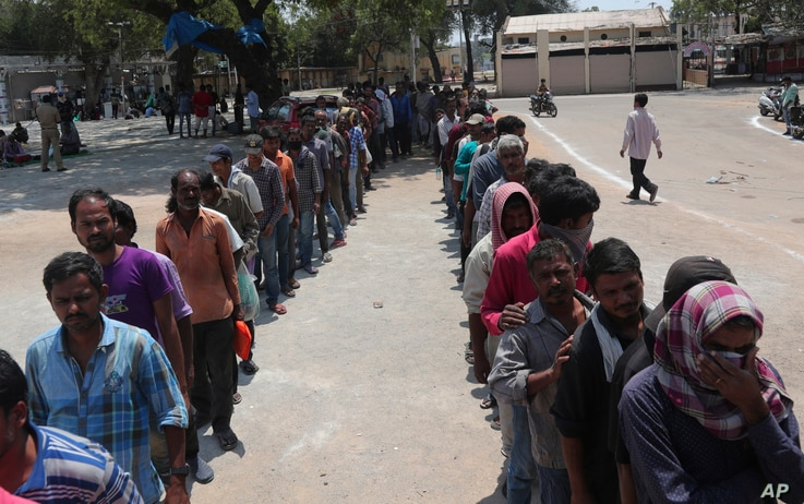 Impoverished Indians stand in queues to receive free food in Hyderabad, India, Friday, March 27, 2020. Some of India's legions…