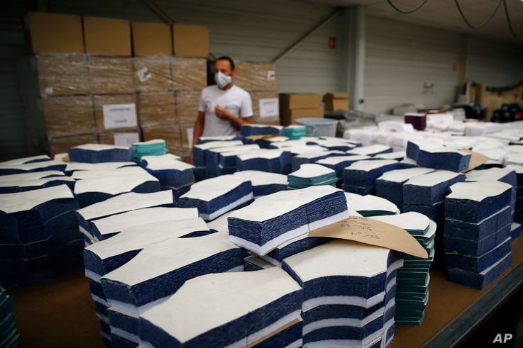 In this Friday, June 12, 2020 photo, an employee walks by fabric cut to produce face protection masks in Chanteclair Hosiery, a…