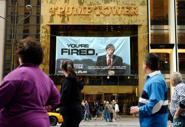 """FILE - In this Saturday, March 27, 2004 file photo, passersby look at a sign advertising the reality television show, """"The…"""