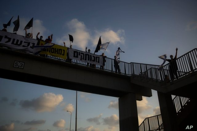 Israeli protesters hold flags and signs as they stand on a bridge to demonstrate against Israel's Prime Minister Benjamin…
