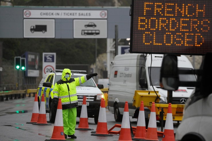 Security guard the entrance to the ferry terminal in Dover, England, Monday, Dec. 21, 2020, after the Port of Dover was closed…