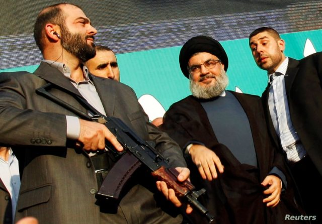 FILE PHOTO: Lebanon's Hezbollah leader Sayyed Hassan Nasrallah (2nd R), escorted by his bodyguards, greets his supporters at an anti-U.S. protest in Beirut's southern suburbs