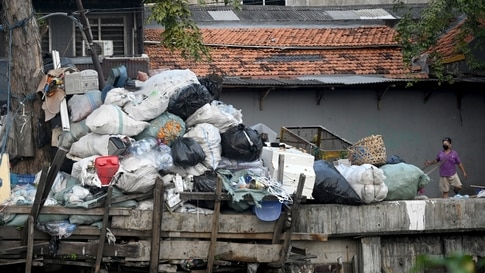 Garbage is seen at a neighbourhood along a canal during Earth Day in Jakarta on April 22, 2021. (Photo by Goh Chai Hin / AFP)