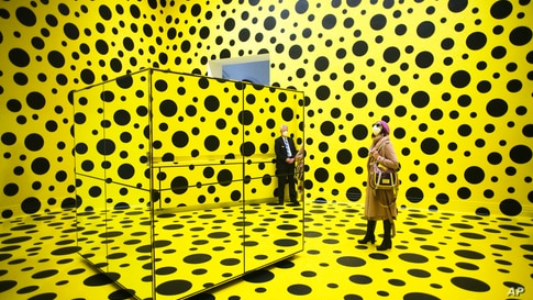 People walk through the art work 'THE SPIRITS OF THE PUMPKINS DESCENDED INTO THE HEAVENS' by Yayoi Kusama, during the press…