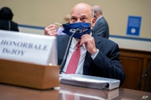 Postmaster General Louis DeJoy removes his face mask as he arrives to testify before a House Oversight and Reform Committee…