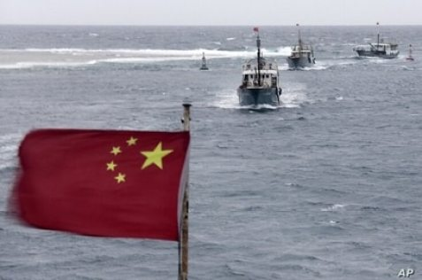 FILE - Chinese fishing boats sail in the lagoon off the island province of Hainan in the South China Sea, July 20, 2012.