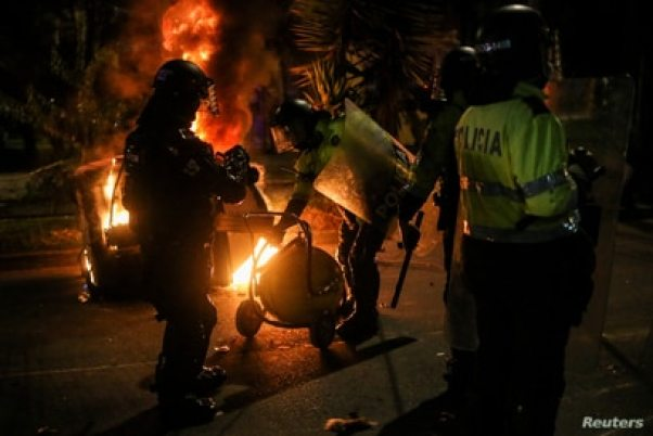 Police officers attempt to extinguish fire from a burning dumpster during a protest after a man, who was detained for violating social distancing rules, died from being repeatedly shocked with a stun gun by officers, according to authorities, in Bogota