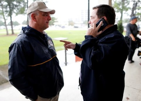 FILE PHOTO: Louisiana Governor John Bel Edwards (L) and Lt. Governor Billy Nungesser talk as Tropical Storm Harvey approaches the area in Lake Charles