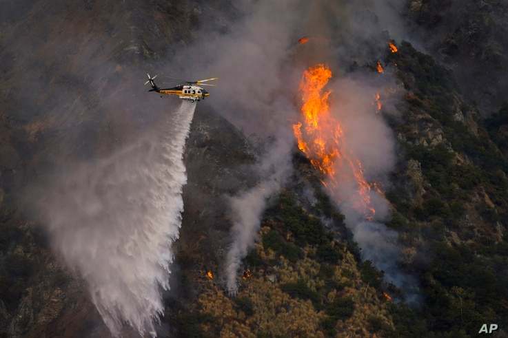 A helicopter makes a water drop over the Ranch Fire, Thursday, Aug. 13, 2020, in Azusa, Calif. Heat wave conditions were making…