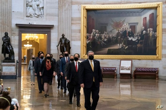 Acting Sergeant at Arms Timothy Blodgett, right, leads Rep. Jamie Raskin, D-Md., second from right, the lead Democratic House…