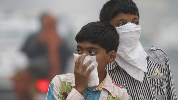 One-way traffic: children hold cloths over their faces as pollution covers New Delhi