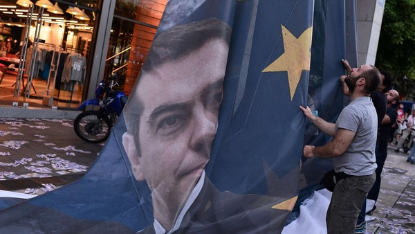 """TOPSHOTS Protesters take down a huge banner bearing a picture of Greek Prime Minister Alexis Tsipras on a European Union flag from the ministry of finance in Athens as they end the occupation of the building on June 11, 2015. The Greek government on Thursday said it would """"intensify"""" efforts to resolve differences with its EU-IMF creditors to reach a deal that would give the country desperately needed bailout funds. AFP PHOTO / LOUISA GOULIAMAKILOUISA GOULIAMAKI/AFP/Getty Images"""