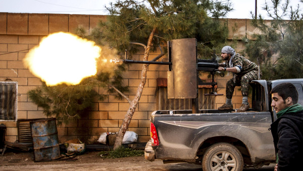 """A Kurdish People's Protection Units (YPG) fighter fires an anti-aircraft weapon at Islamic State fighters in Tel Tawil village, Syria, in this February 25, 2015 file photo. A conference underway in Kurdish-controlled northern Syria aims to approve a """"Federal Democratic"""" system of government for the area. REUTERS/Rodi Said/Files"""