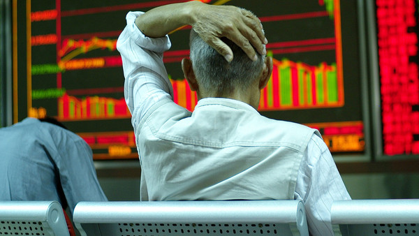 A stock investor sits in front of an electronic screen showing stock price at a brokerage house in Beijing