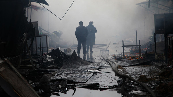 People walk past burnt out kiosks at a street market close to a destroyed building housing the housing the local media known as the Press House, in central Grozny, on December 4, 2014. Heavily-armed gunmen attacked a police post killing several officers before storming a building housing the local media and a school in the capital. AFP PHOTO/ELENA FITKULINA
