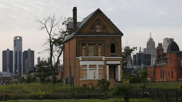 A boarded up vacant home is seen with General Motors World Headquarters (L) and the Detroit skyline June 10, 2014. REUTERS/Rebecca Cook (UNITED STATES - Tags: TRANSPORT BUSINESS)