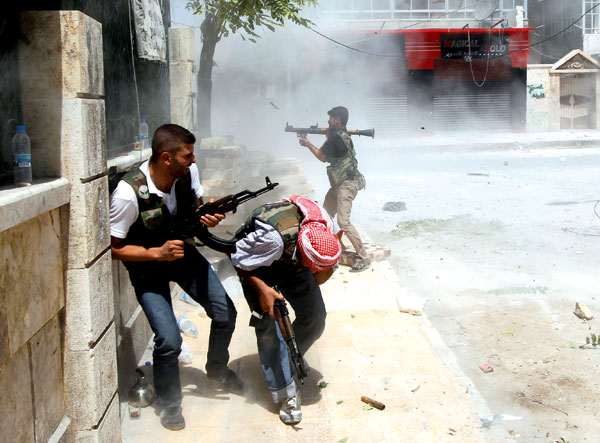 A Free Syrian Army fighter fires a RPG as a Syrian Army tank shell hits a building across a street during heavy fighting in the Salaheddine neighbourhood of central Aleppo August 11 2012