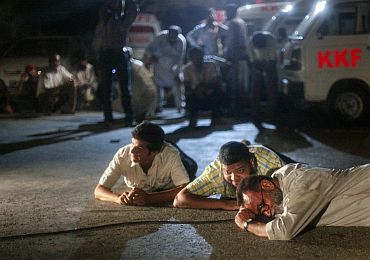 A file photo of rescue workers and journalists taking cover outside Mehran naval aviation base