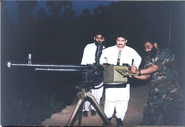 Exclusive Image: Ilyas Kashmiri (extreme right) shows an anti-aircraft gun to Hamid Mir (centre)