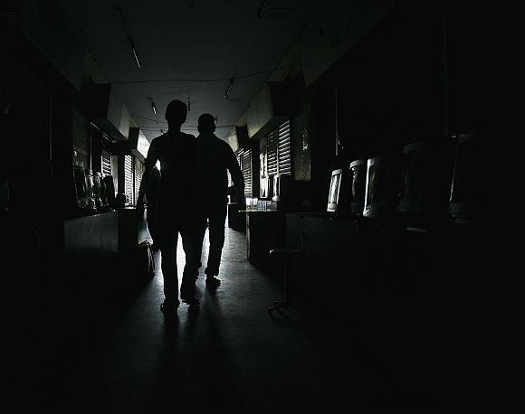 Los Hombres Se perfilan while caminaba Por Un Mercado de las Computadoras Durante la ONU corte de luz en Karachi