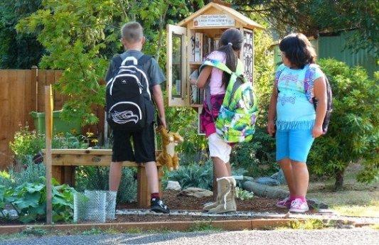 Niños mirando una pequeña biblioteca libre.