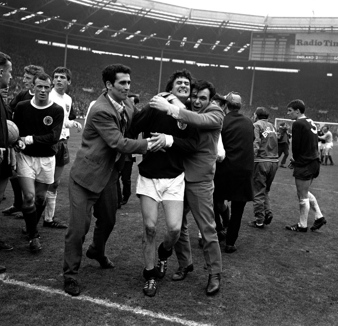 Scotland's Jim Baxter (centre) is enthusiastically hugged by overjoyed fans who invaded the Wembley Stadium pitch after England had been beaten 3-2 in 1967