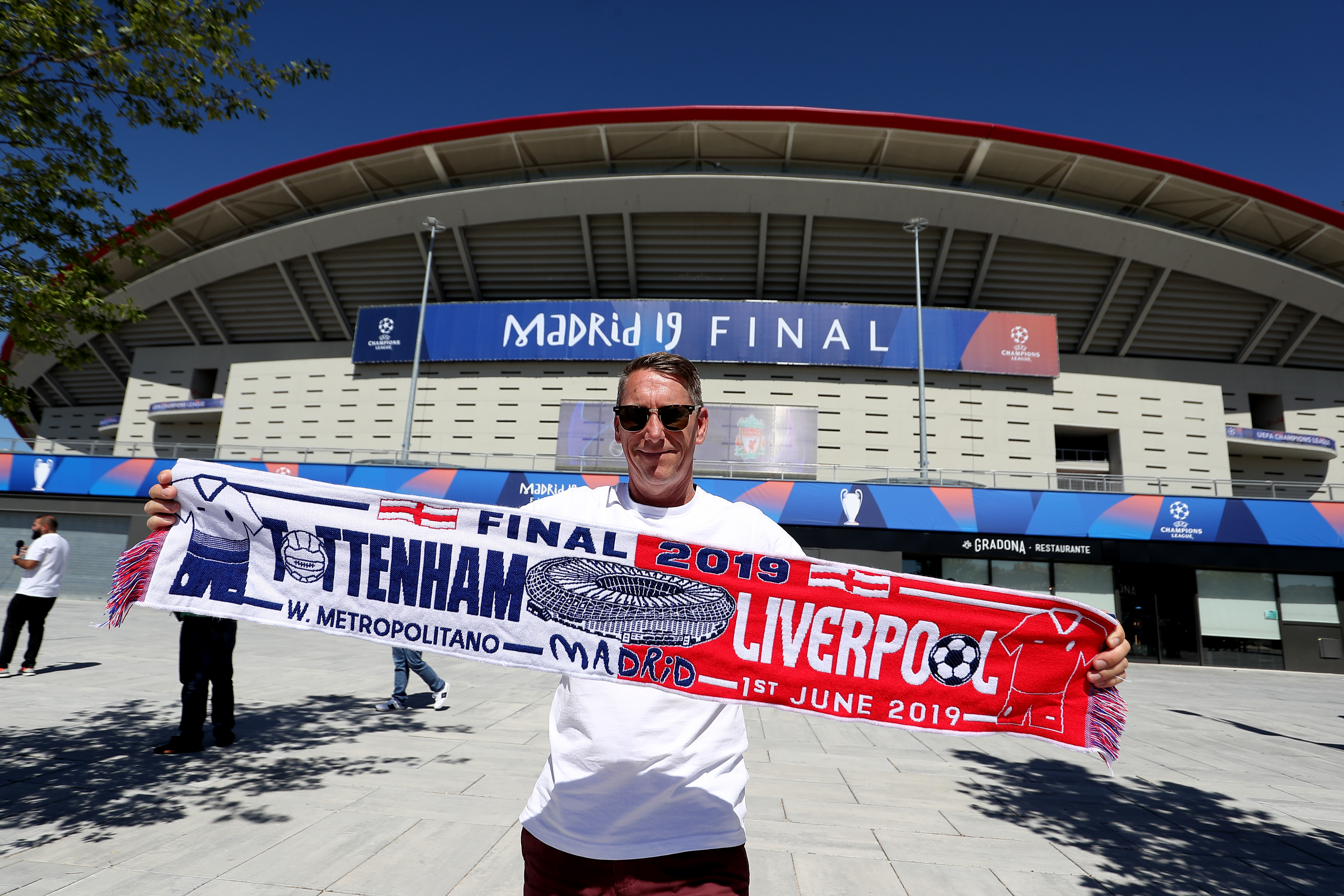 A Tottenham fan with a half-and-half scarf in front of the Wanda Metropolitano