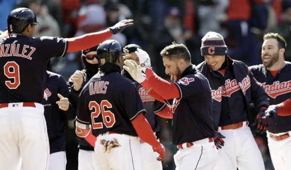 Cleveland Indians' Yan Gomes, center, is congratulated by teammates after hitting a two-run home run off Kansas City Royals relief pitcher Brandon Maurer in the ninth inning.