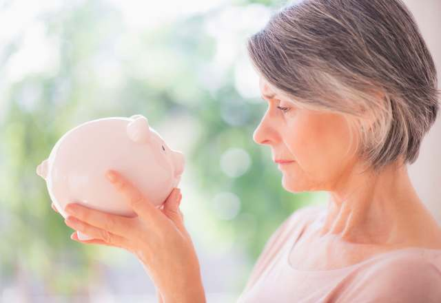 Premium: Middle aged woman holding piggy bank retirement savings