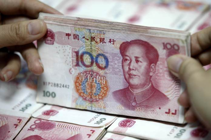 A Chinese clerk counts renminbi yuan banknotes at a bank in China on December 2015.