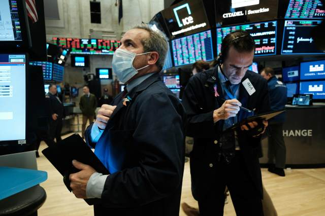 Traders, some in medical masks, work on the floor of the New York Stock Exchange (NYSE) on March 20, 2020 in New York City. Trading on the floor will temporarily become fully electronic starting on Monday to protect employees from spreading the coronaviru