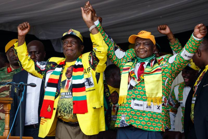 "MUROMBEDZI, Zimbabwe, November 24, 2018: Zimbabwe's President Emmerson Mnangagwa (L) holds hands with Zimbabwe's Vice President Constantino Chiwenga (R) as they salute a crowd during a ""Thank You"" rally."