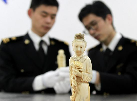 Customs officers display a seized ivory figurine intercepted in a package from Europe in Qingdao, Shandong Province, in March. (Photo by ZHANG JINGANG/FOR CHINA DAILY)
