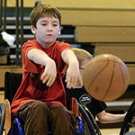 boy in wheelchair playing basketball