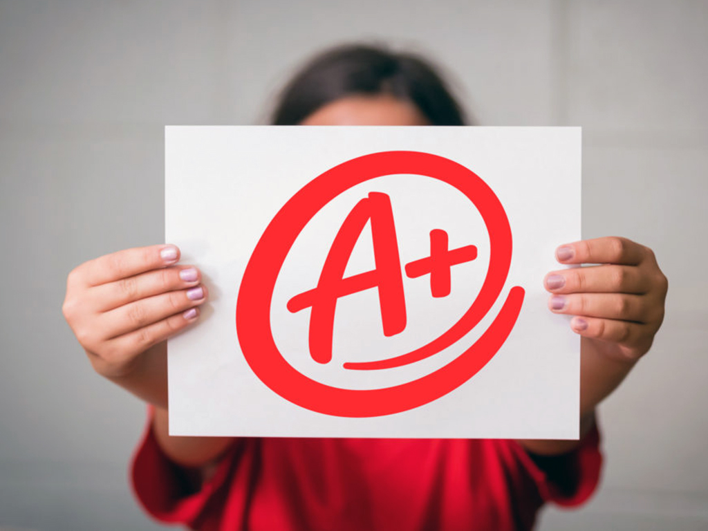 student holding sign saying A+